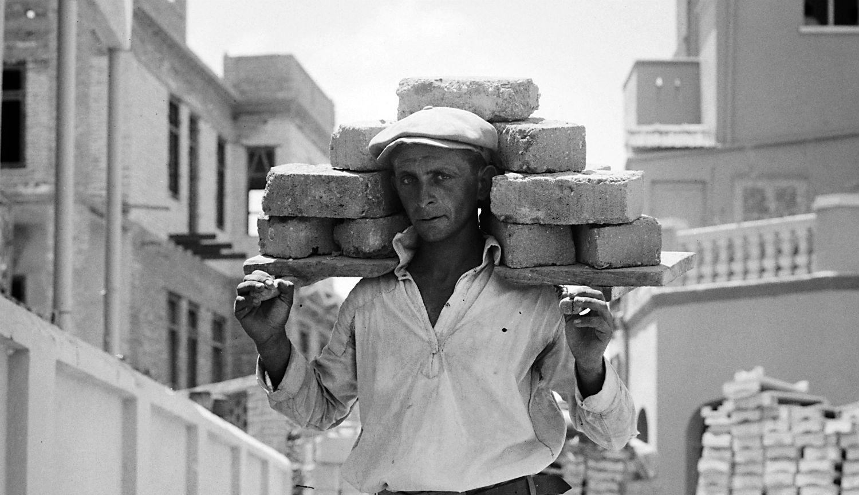 A man carrying bricks in 1920s Tel Aviv.Library of Congress.